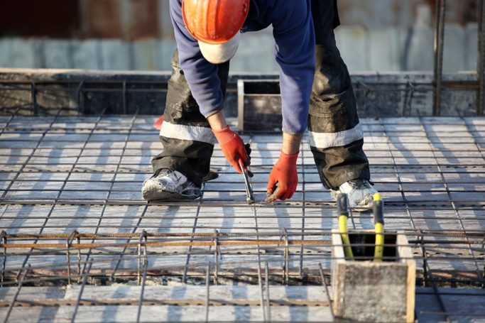 Construction worker placing rebar on project site